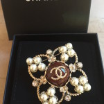 This metal brooch with stress, resin and glass pearls is perfect for that classic touch in any outfit.